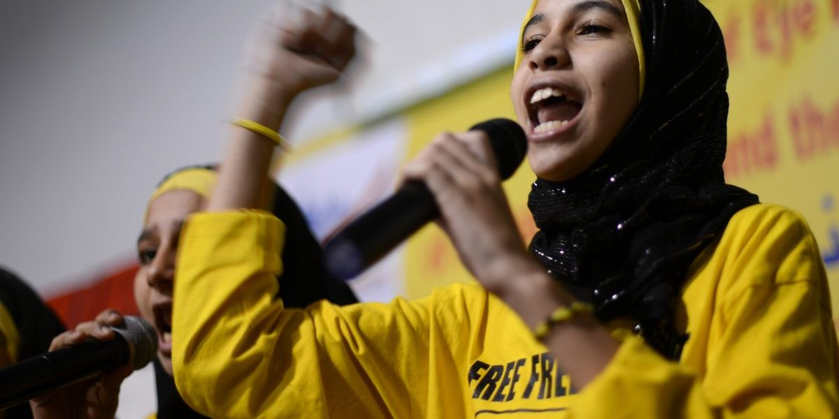 Image: A young Egyptian reads a poem during the protest meeting against the military coup in Egypt to support Egypt's first freely elected president, Mohamed Morsi, who was removed from power by the military on November 17, 2013 in New Jersey, United States (Cem Ozdel /Anadolu Agency/Getty)