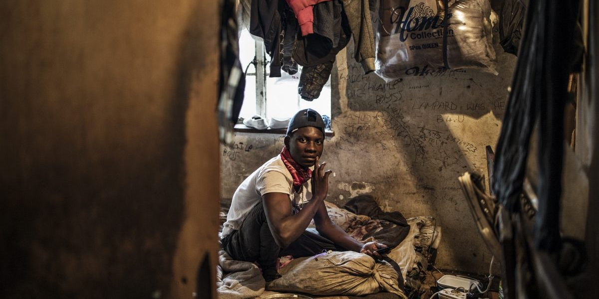 A foreign migrant sits on his bed inside a boarded up room occupied by two people on the upstairs floor in a building in the Kwa Mai Mai area in Johannesburg. Image: Getty, Marco Longari/AFP
