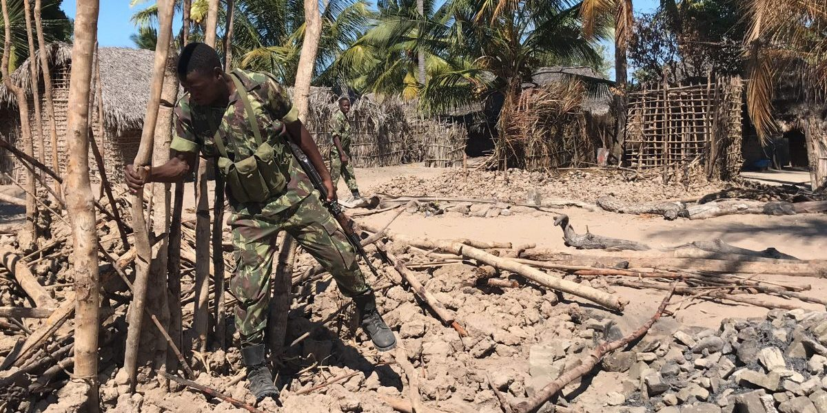 Mozambican Army soldiers bring down a structure torched by attackers, to be rebuilt as shelter for people fleeing the recent attacks, in Naunde, northern Mozambique, on June 13, 2018. Image: Getty, Joaquim Nhamirre/AFP