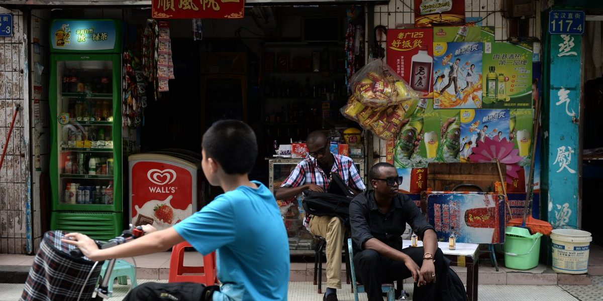 Traders from Africa rest outside a convenience store in Guangzhou.          Image: Getty, STR/AFP