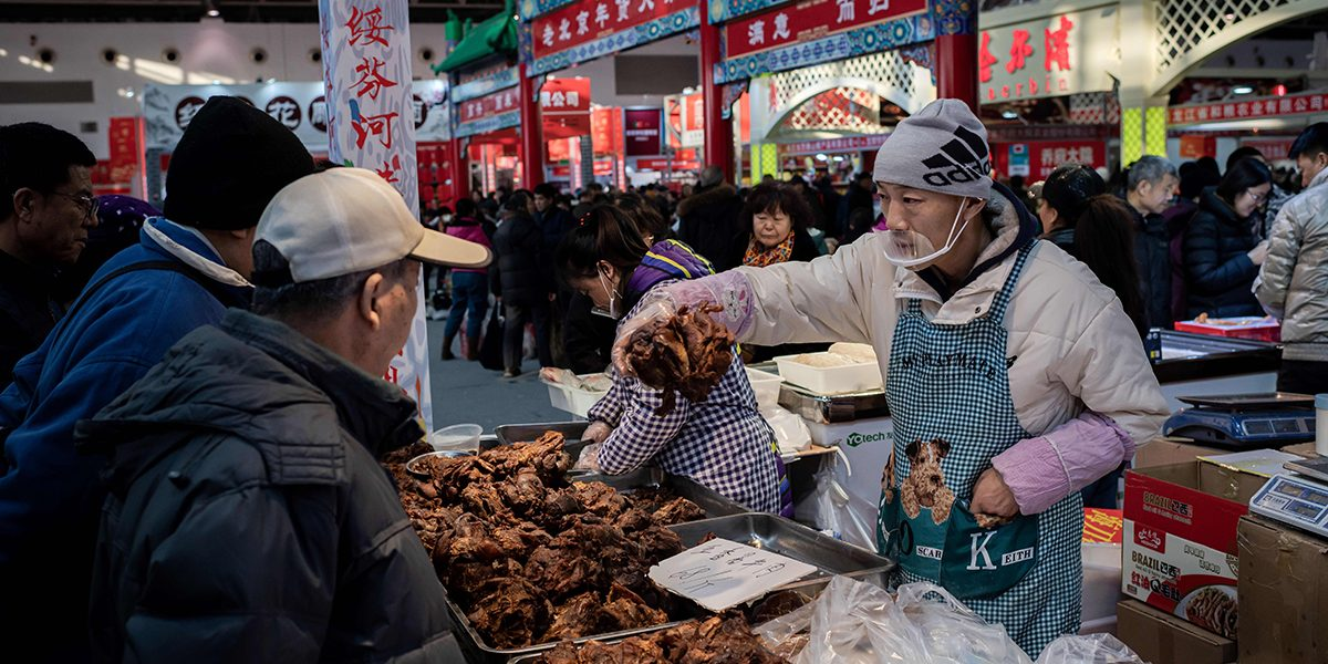 A vendor selling meat to customers at a market in Beijing in January 2020. Image: Getty, Nicolas Asfouri / AFP