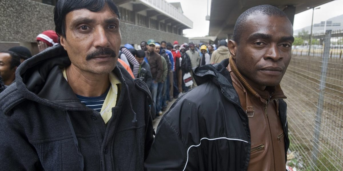 Hundreds of refugees queue outside the South African Department of Home Affairs to apply for extensions of their asylum seeker permits, in Cape Town. Image: Getty Images, Rodger Bosch/AFP