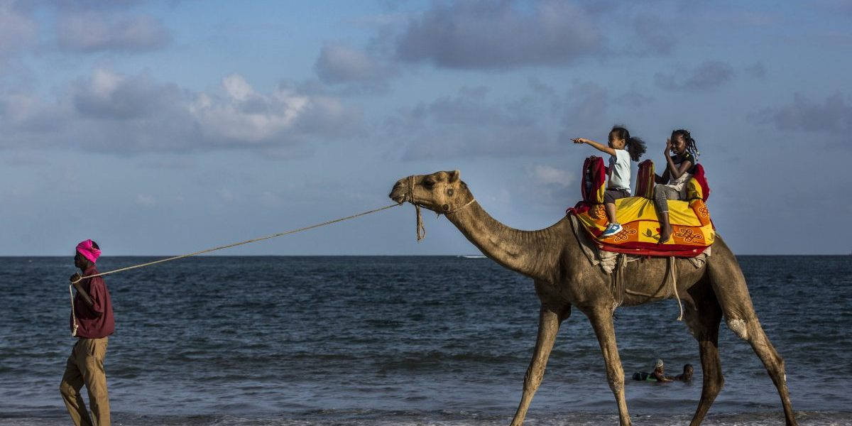 A vendor leads a camel carrying two children along the beachfront in Mombasa, Kenya. Image: Getty, Luis Tato/Bloomberg,