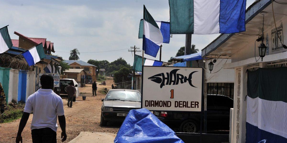 A resident walks by a diamond dealer's shop in Koidu, the capital of the diamond-rich Kono district, in eastern Sierra Leone, April 2012. Image: Getty Issouf Sanogo/AFP