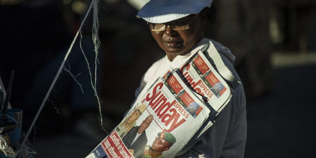 A newspaper seller is pictured on August 31, 2014 in Maseru. Lesotho Prime Minister Tom Thabane claimed on August 30 he fled for his life after soldiers seized power in a coup, despite the military denying it overthrew the tiny mountain kingdom's government. Image: Getty,  Mujahid Safodien/AFP