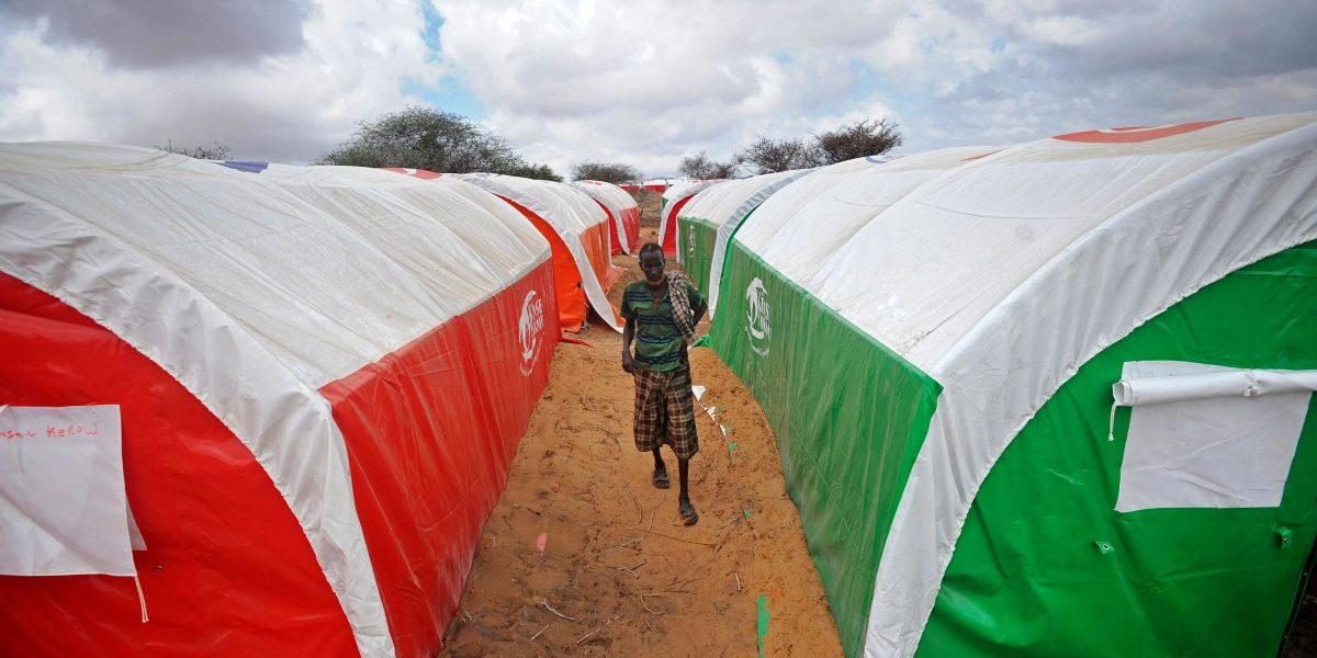A newly displaced Somali man walks between tents at a camp in the Kaxda district, outskirts of Mogadishu. Image: Getty, Mohamed Abdiwahab/AFP