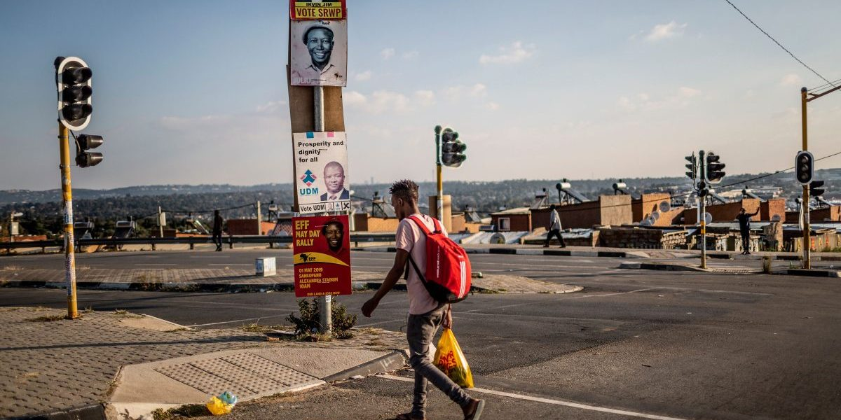 A street scene shows a man crossing the road flanked by South African political party posters in the run up to elections on April 28, 2019 in Alexandra, Johannesburg. Image: Getty,  Gulshan Khan/AFP