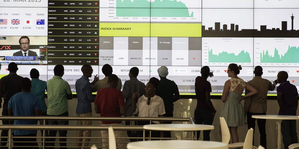 People from a school group look at an electronic screen with stock index figures at the Johannesburg Stock Exchange (JSE) in Johannesburg, South Africa. Image: Getty, Gianluigi Guercia/AFP