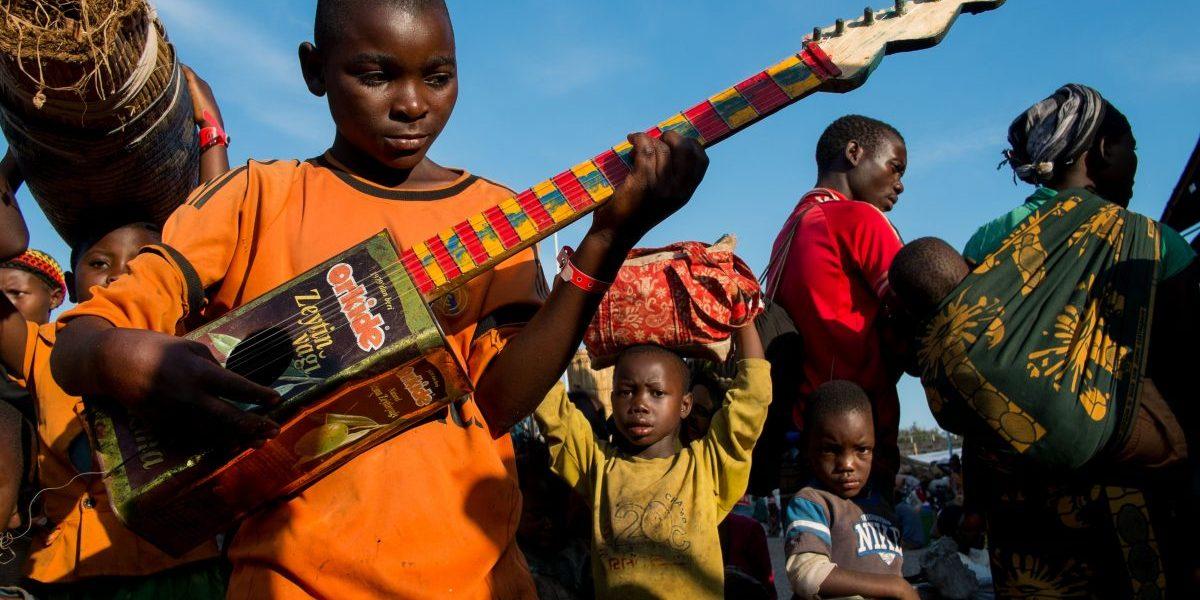 Burundian refugee Richard Samuel, 14, plays his home made guitar as he waits to be transferred to Nyarugusu Refugee Camp from Lake Tanganyika Stadium in Kigoma. Image: Getty, Daniel Hayduk/AFP