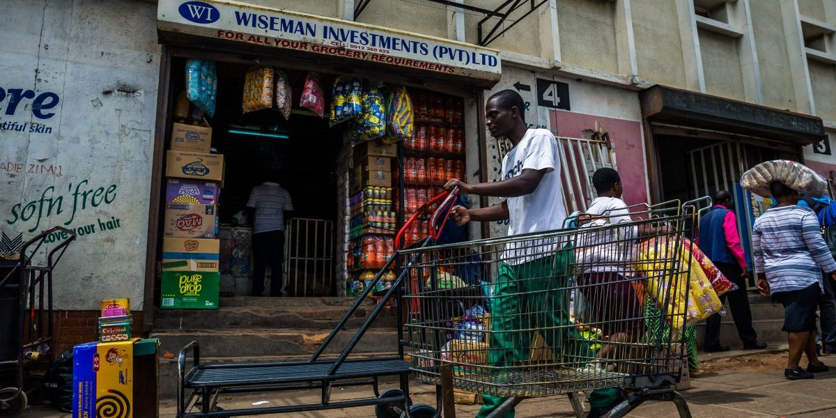A man pushes a cart through a market as business continues in the Zimbabwean capital, Harare, on 16 November 2017, a day after the military announced plans to arrest 'criminals' close to the president. Zimbabweans faced an uncertain future after the army took power and placed President Mugabe, a liberation hero turned authoritarian leader, under house arrest. Image: Getty, STR/AFP