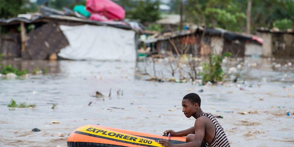 A man uses a rubber dinghy to navigate through the flooded Jangwani neighbourhood in Dar es Salaam, Tanzania. Image: Getty, Daniel Hayduk/AFP