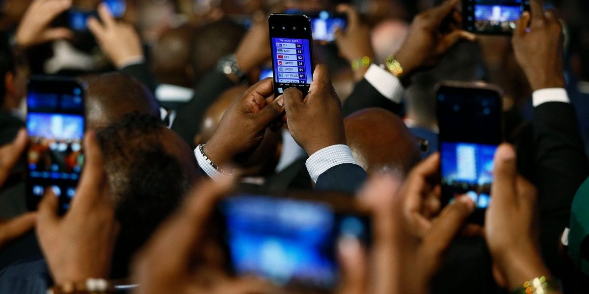 People take pictures with mobile phones during the formal announcement of the National and Provincial Election Results at the Independent Electoral Commission (IEC) Results Operations Centre on 11 May 2019 in Pretoria, South Africa. Image: Getty, Phill Magakoe/AFP