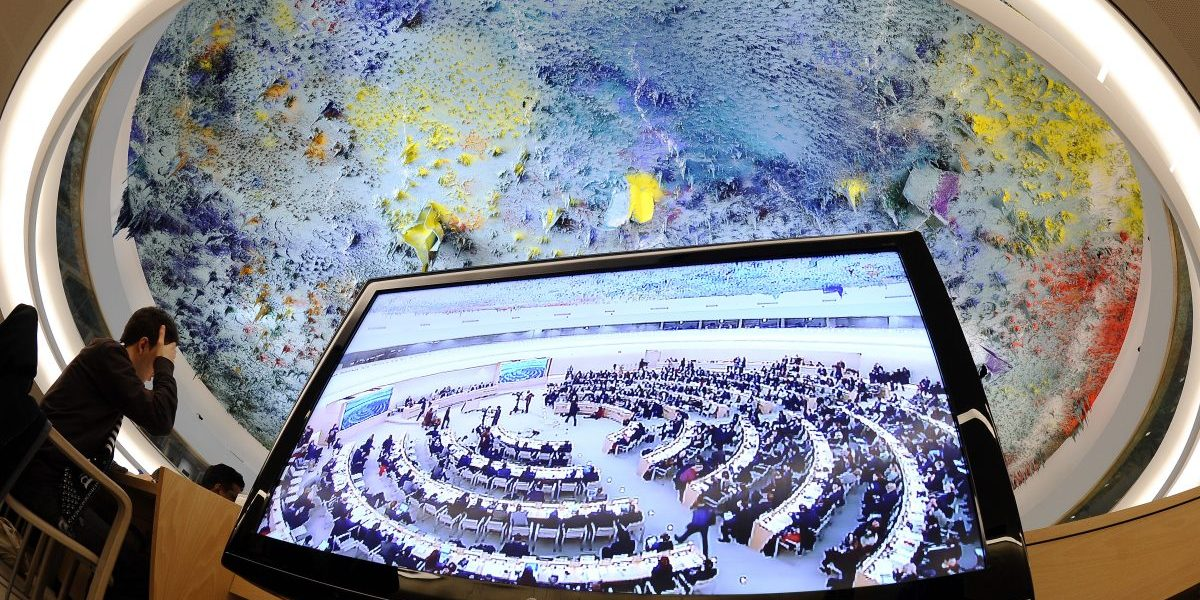 The assembly hall seen on a television screen during the opening of the 16th session of the United Nations Human Rights Council in Geneva, focusing on repression in Libya. Image: Getty, Fabrice Coffrini/AFP