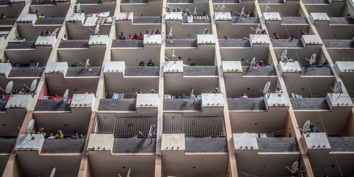 Residents of a Hillbrow, Johannesburg, building observe from the balconies on March 28, 2020 as a police operation is conducted to make sure everyone observes the Country's lockdown, South Africa. Image, Getty, Marco Longari/Contributor