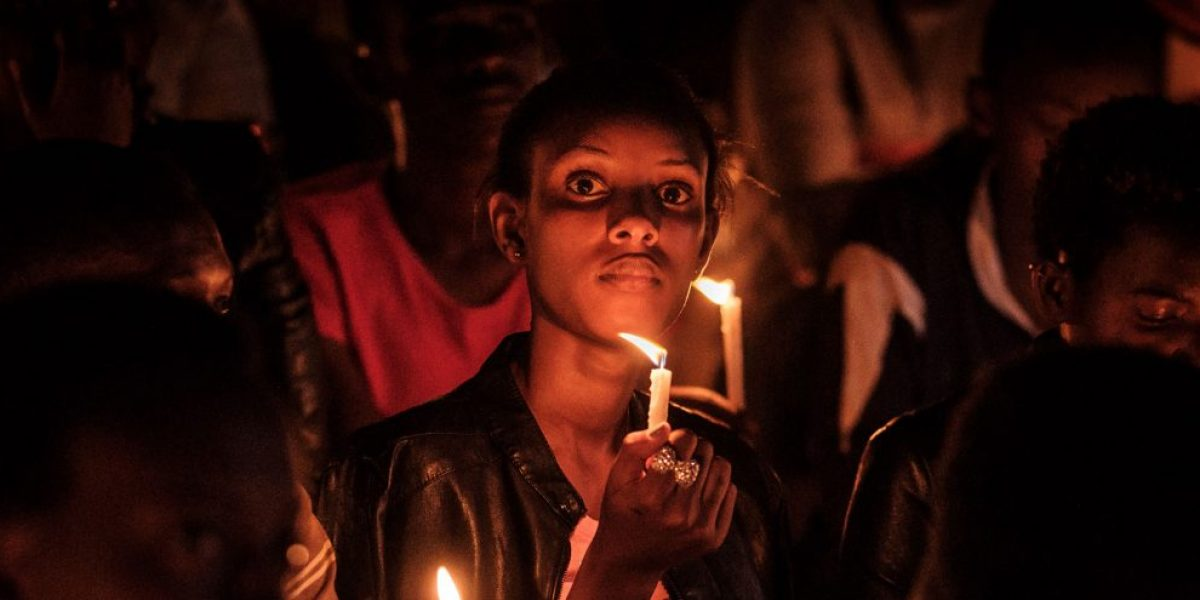 A woman holds a candle during a night vigil and prayer at the Amahoro Stadium as part of the 25th Commemoration of the 1994 Genocide, in Kigali, Rwanda, on 7 April 7, 2019. Image: Getty, Yasuyoshi Chiba / AFP